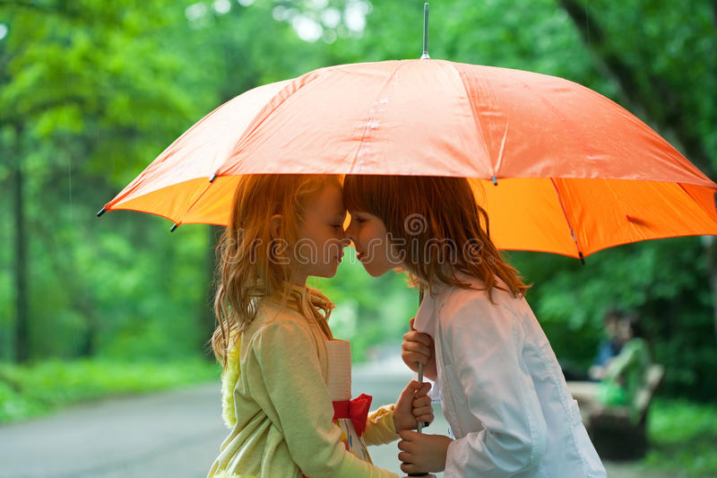 Niños bajo un paraguas foto de archivo libre de regalías