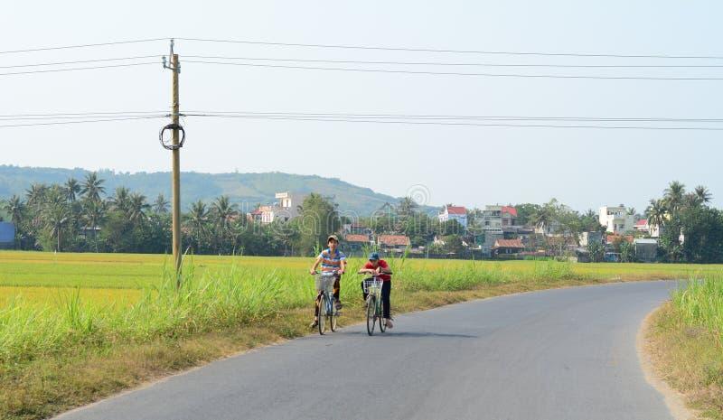 Niños biking en el camino rural en Phuyen, Vietnam fotos de archivo libres de regalías