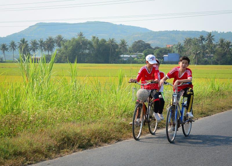 Niños biking en la calle en el delta del Mekong, Vietnam fotografía de archivo