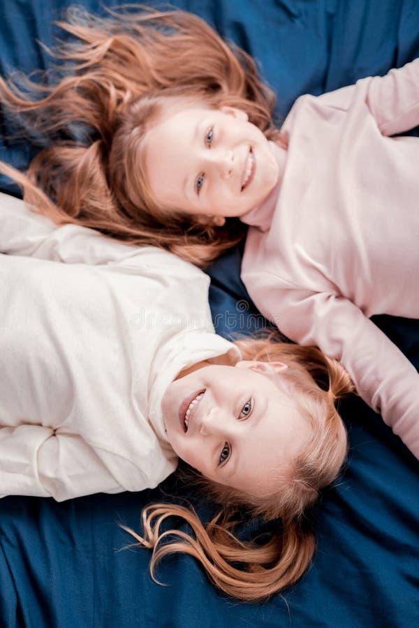 Niños bonitos que ponen en la cama fotografía de archivo libre de regalías