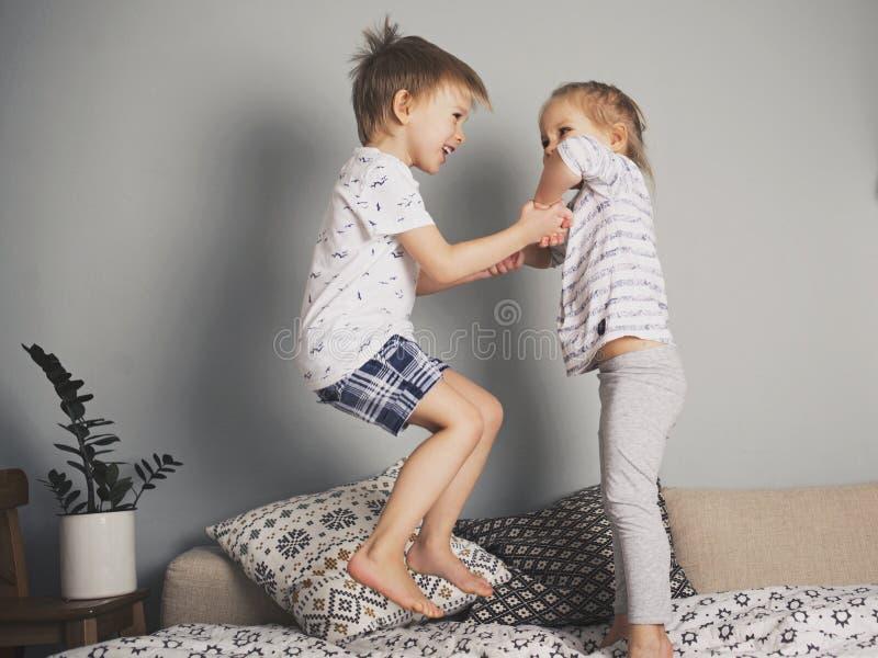 Niños bonitos que saltan en la cama junto imagen de archivo libre de regalías
