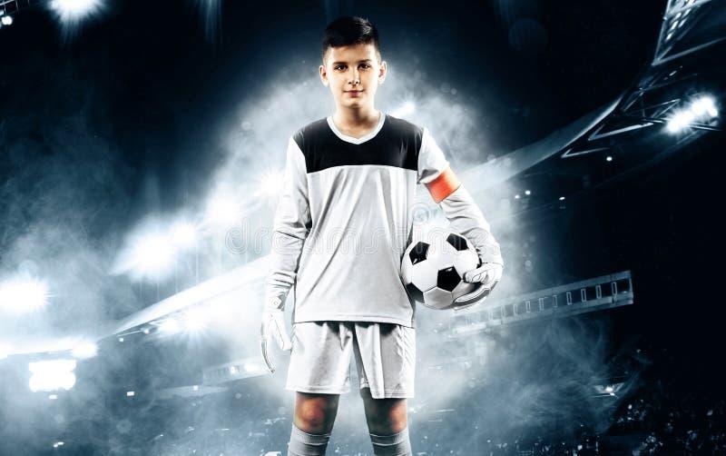 Niños - campeón del fútbol Portero del muchacho en ropa de deportes del fútbol en estadio con la bola Concepto del deporte fotografía de archivo