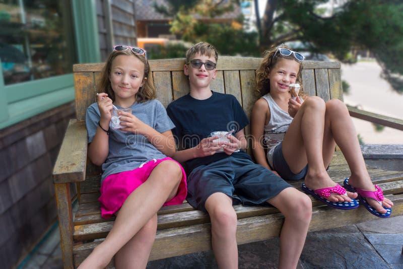 Niños comiendo helados en verano al aire libre foto de archivo