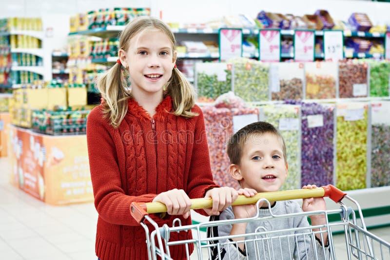 Niños con compras del carro fotografía de archivo