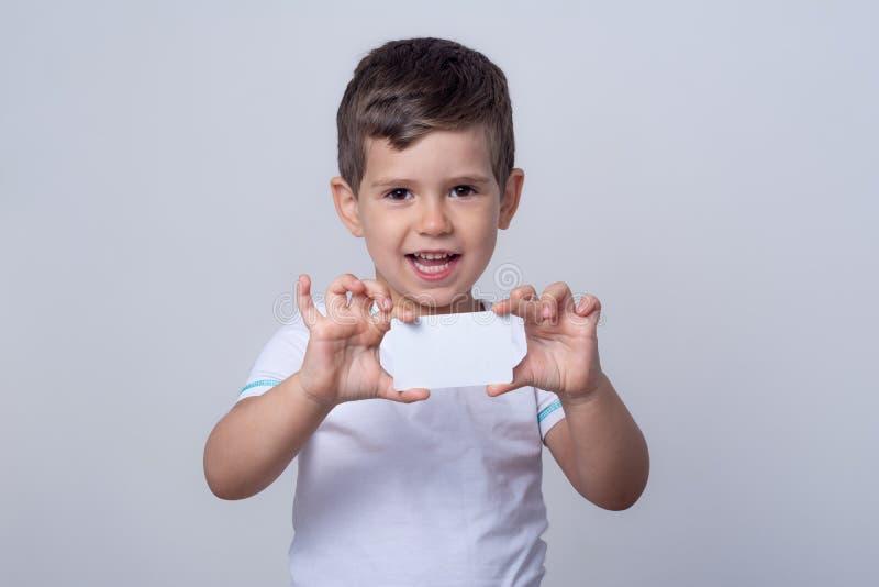 Niños con descuento tarjeta blanca en la mano. Niño con tarjeta de crédito. Pequeño niño que muestra espacio vacío en la cop foto de archivo libre de regalías