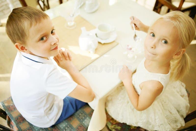 Niños con el postre en café fotos de archivo