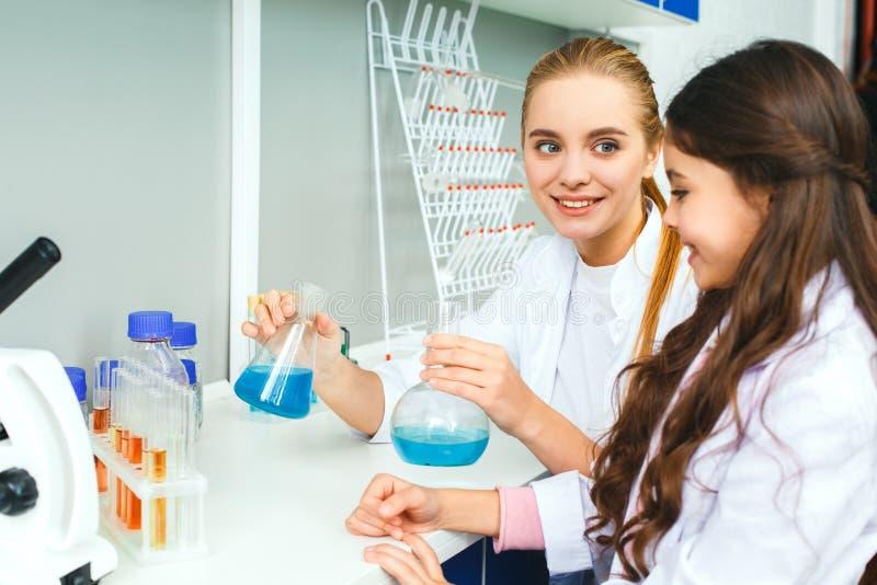 Niños con el profesor en el laboratorio de la escuela que muestra el experimento fotografía de archivo libre de regalías