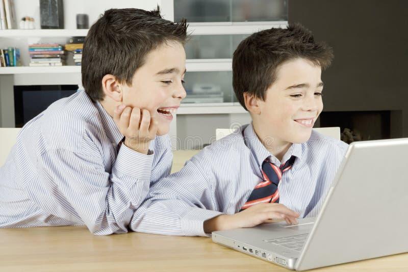 Niños con la computadora portátil en casa foto de archivo libre de regalías