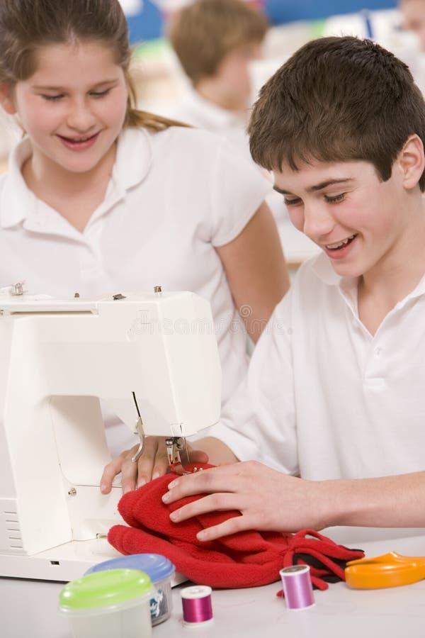 Niños con la máquina de coser fotos de archivo