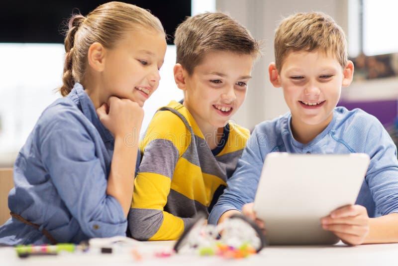 Niños con la PC de la tableta que programa en la escuela de la robótica imagenes de archivo