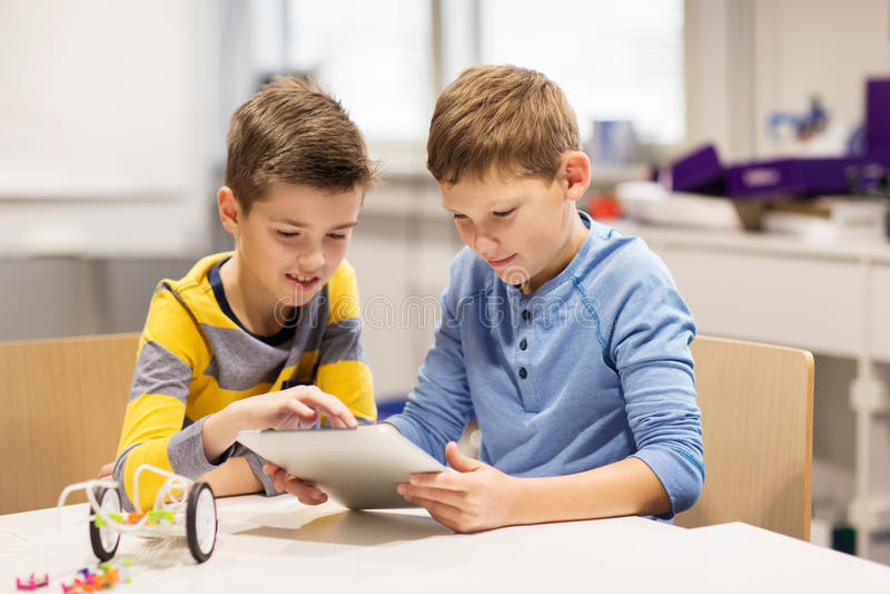 Niños con la PC de la tableta que programa en la escuela de la robótica imágenes de archivo libres de regalías