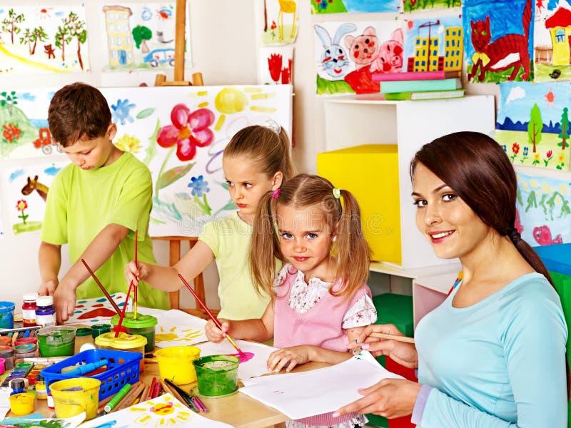 Niños con la pintura del profesor. imagen de archivo