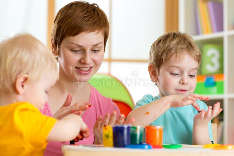 Niños con la pintura del profesor en playschool fotos de archivo