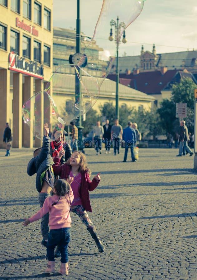 Niños con las burbujas de jabón en la calle imagenes de archivo