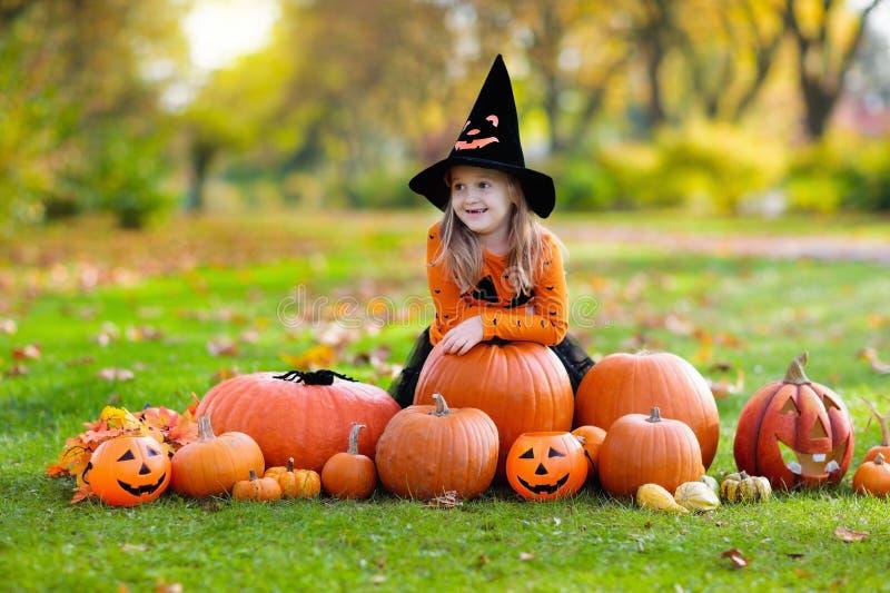 Niños con las calabazas en disfraces de Halloween imágenes de archivo libres de regalías