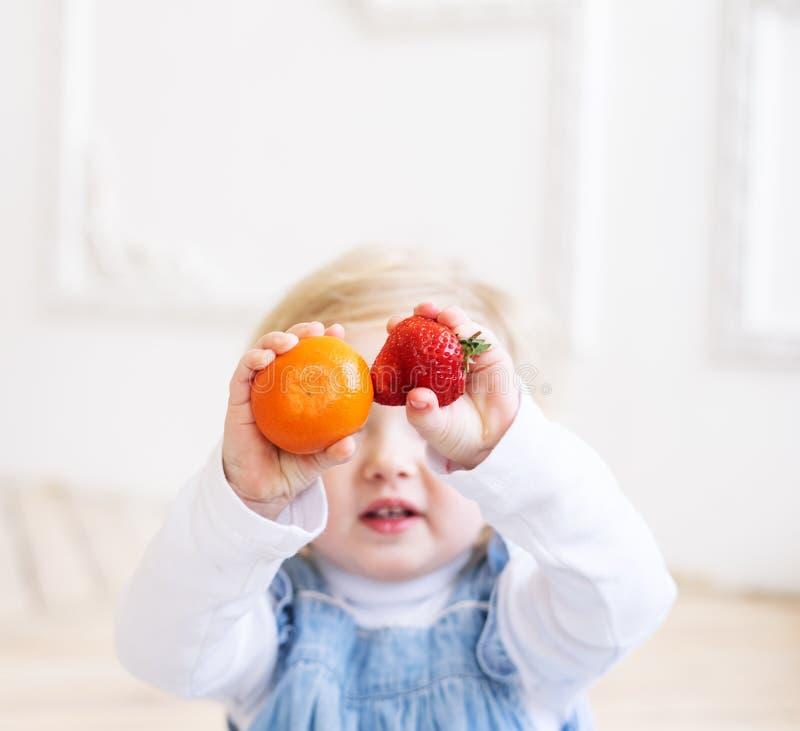 Niños con las frutas: Una niña de dos años en los sundress azules sostiene una fresa roja y una mandarina anaranjada en ella fotos de archivo