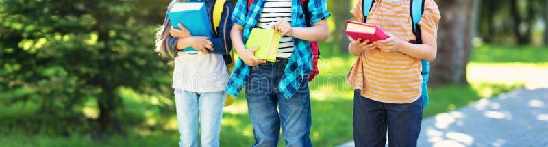 Niños con las mochilas que se colocan en el parque cerca de escuela fotos de archivo