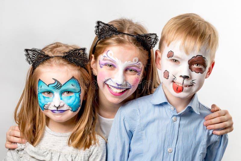 Niños con las pinturas animales de la cara aisladas imagenes de archivo