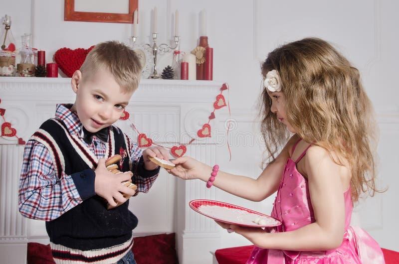 Niños con las tortas en forma de corazón foto de archivo