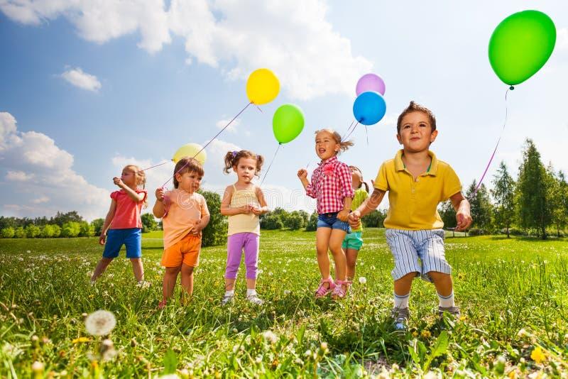 Niños con los globos coloridos que corren en campo foto de archivo libre de regalías