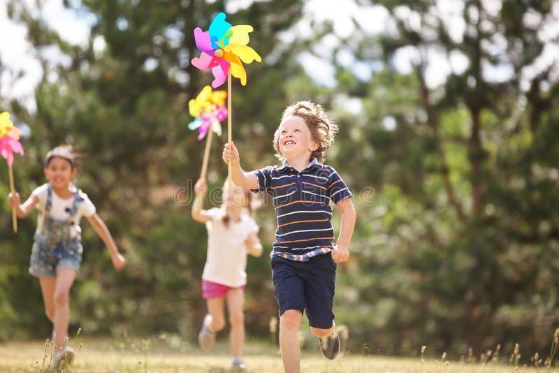 Niños con los molinillos de viento foto de archivo
