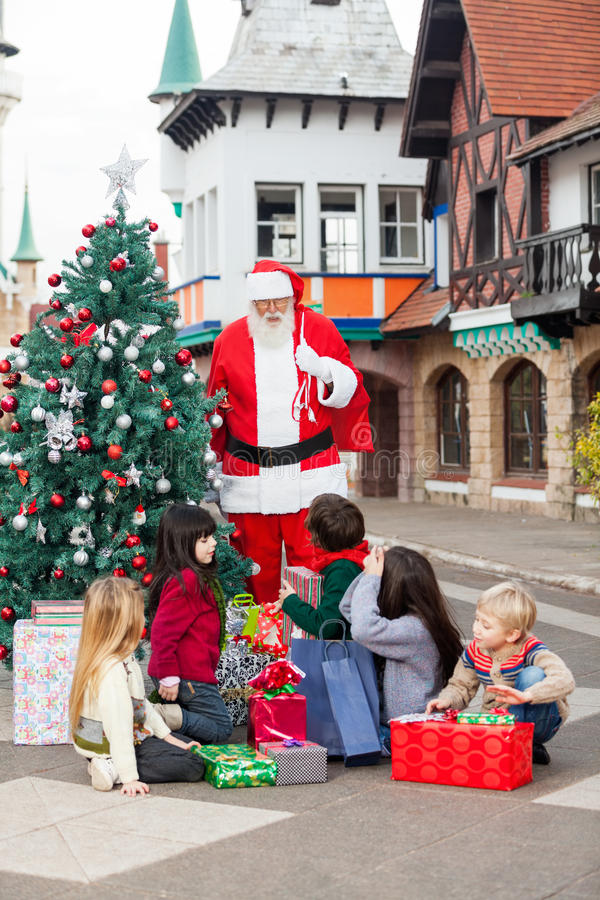 Niños con los regalos que miran a Santa Claus imágenes de archivo libres de regalías