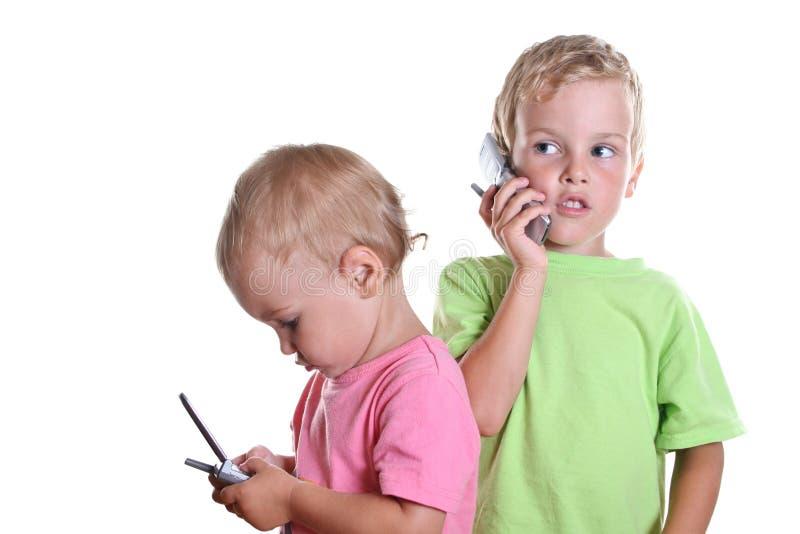 Niños con los teléfonos 2 fotos de archivo