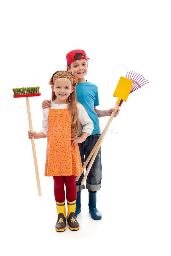 Niños con los utensilios que cultivan un huerto y las botas de goma - aislados fotografía de archivo