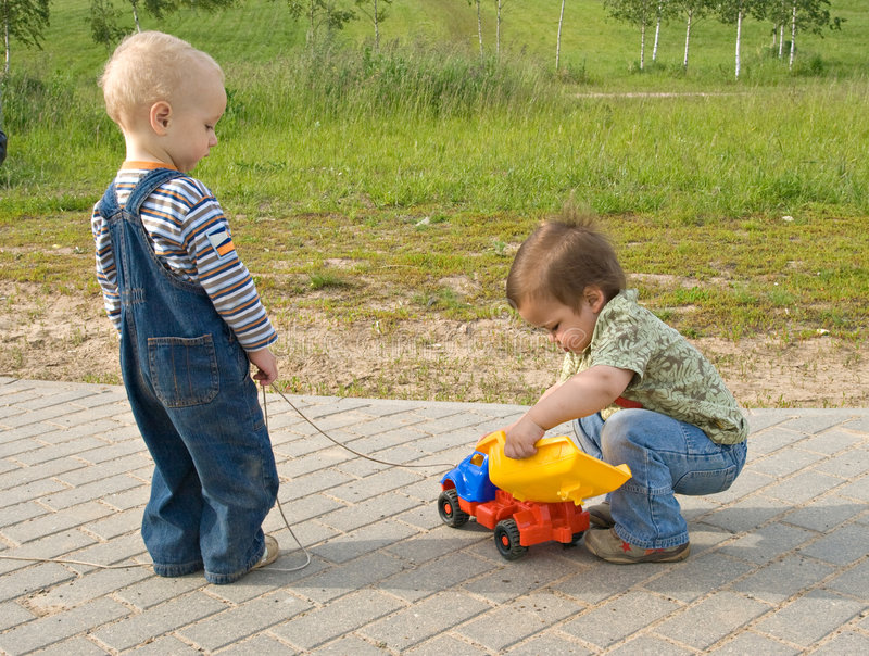 Niños con un carro del juguete imagen de archivo