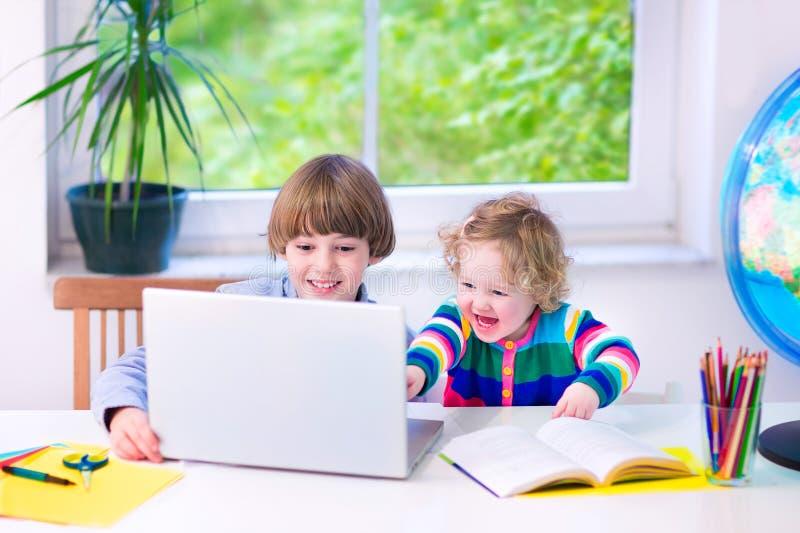 Niños con un ordenador portátil imagen de archivo libre de regalías