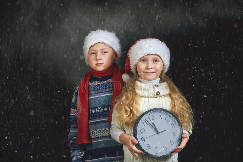 Niños con un reloj y un sombrero de la Navidad en un fondo oscuro foto de archivo libre de regalías