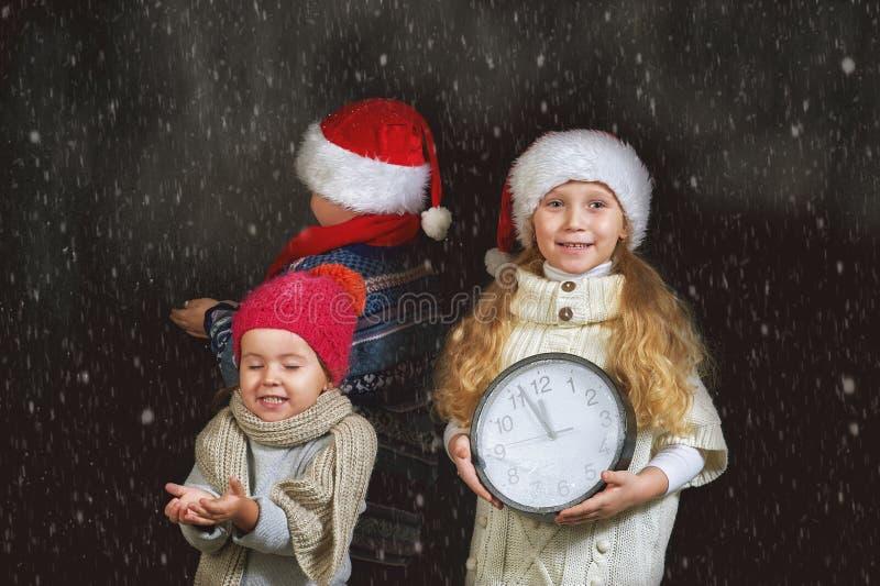 Niños con un reloj y un sombrero de la Navidad en un fondo oscuro imagen de archivo