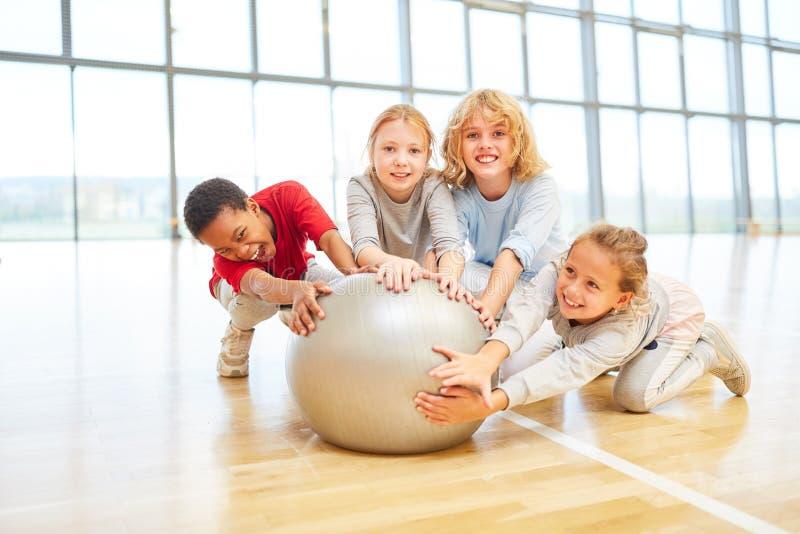 Niños con una bola del gimnasio fotografía de archivo