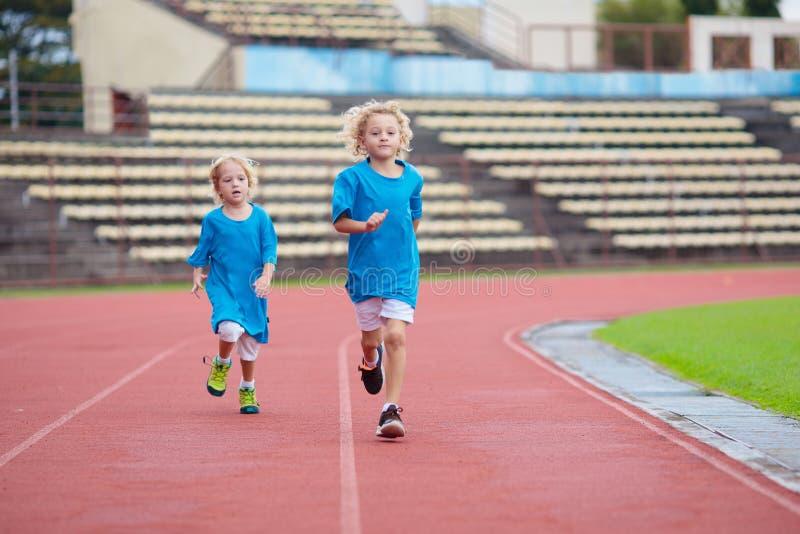 Niños corriendo en el estadio Los niños corren Deporte saludable foto de archivo
