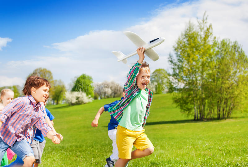 Niños corrientes felices con el juguete blanco del aeroplano imagenes de archivo