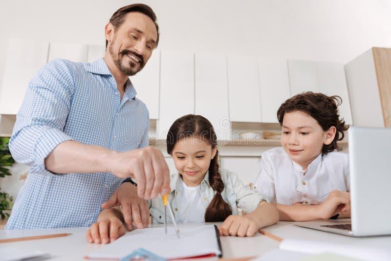 Niños curiosos que miran a su padre que usa el compás fotografía de archivo libre de regalías