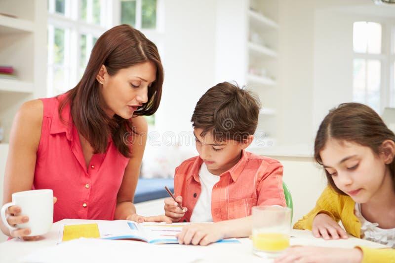 Niños de ayuda de la madre con la preparación imágenes de archivo libres de regalías