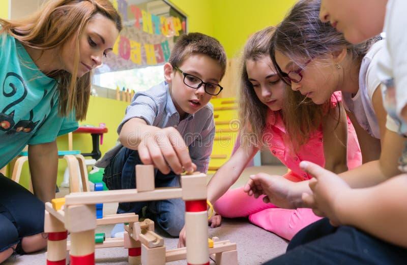 Niños de ayuda del maestro de jardín de infancia dedicado con la construcción de un tren foto de archivo libre de regalías