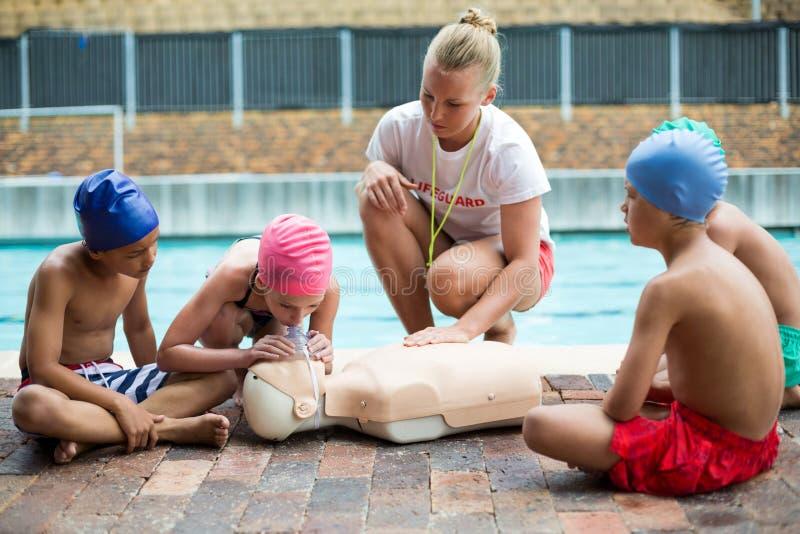 Niños de ayuda del salvavidas durante el entrenamiento del rescate imágenes de archivo libres de regalías
