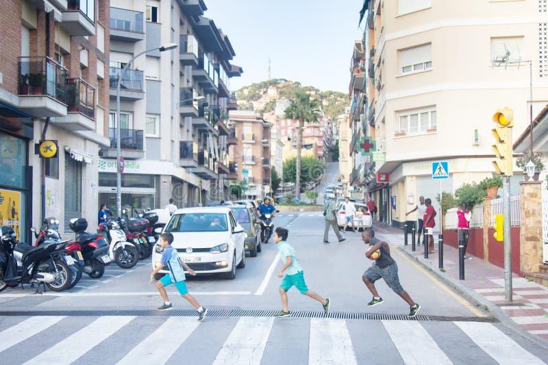 Niños de diferentes razas cruzan la calle con luz verde fotos de archivo