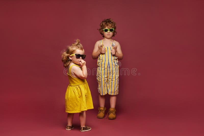 Niños de diseño y elegantes vestidos con un fondo rosa Una niña pequeña con un vestido y gafas de sol y una foto de archivo