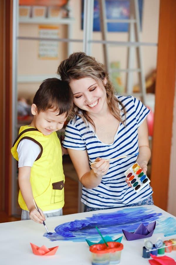 Niños de enseñanza que dibujan, desarrollo de capacidades creativas Dibuje un mar, haciendo papiroflexia Luz del día natural imagenes de archivo
