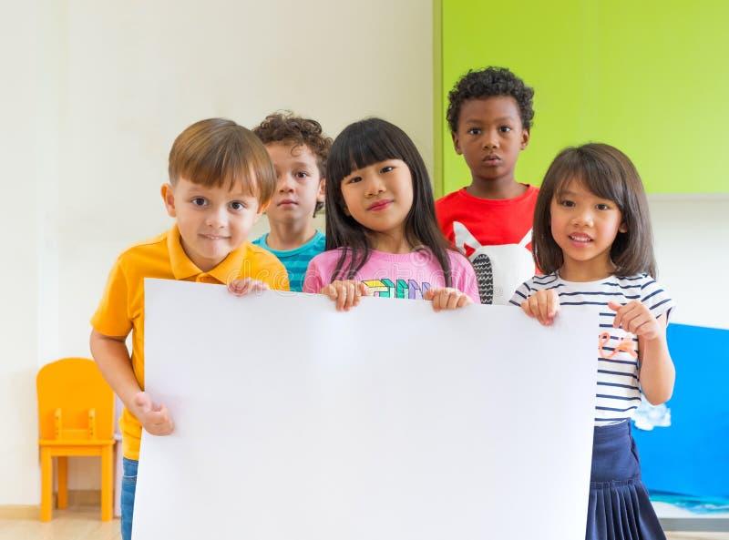 Niños de la diversidad que sostienen el cartel en blanco en sala de clase en el kinderga foto de archivo