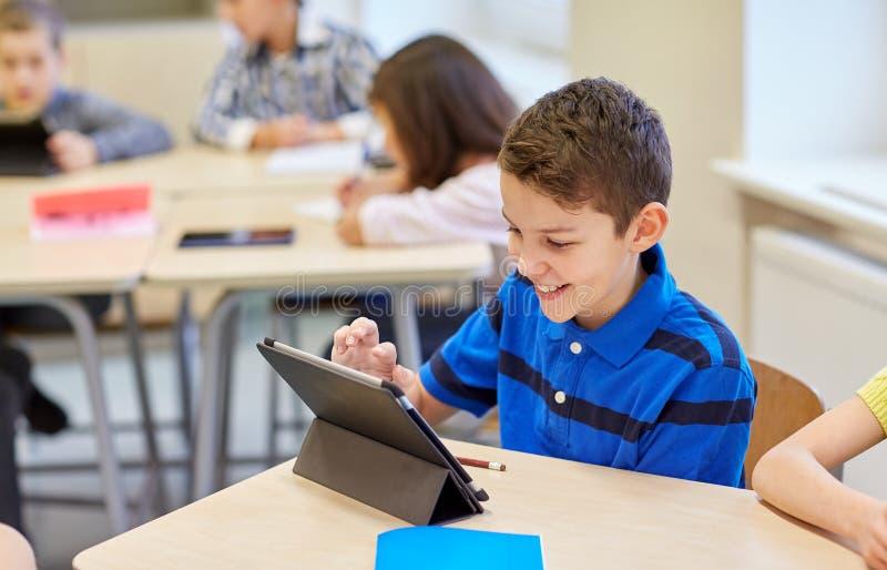 Niños de la escuela con PC de la tableta en sala de clase imágenes de archivo libres de regalías