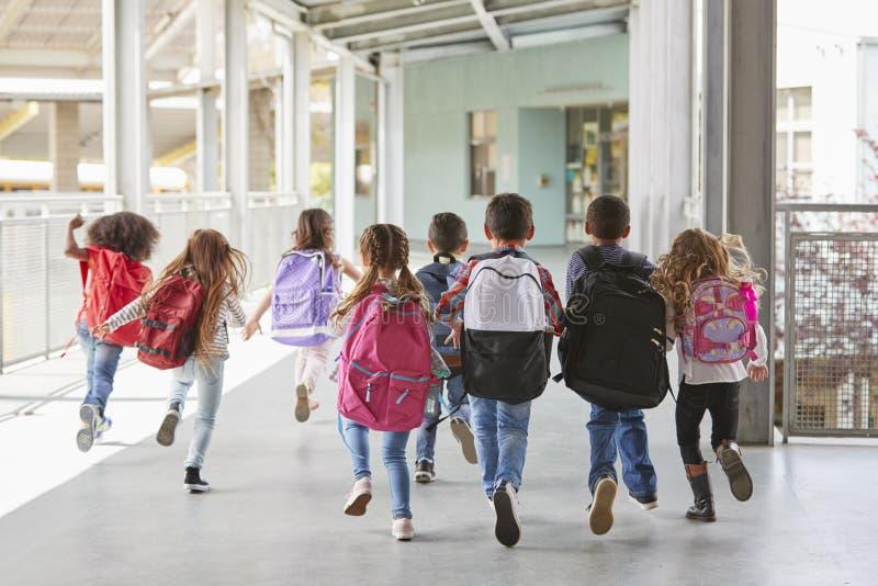 Niños de la escuela primaria funcionados con de cámara en el pasillo, cierre para arriba imágenes de archivo libres de regalías