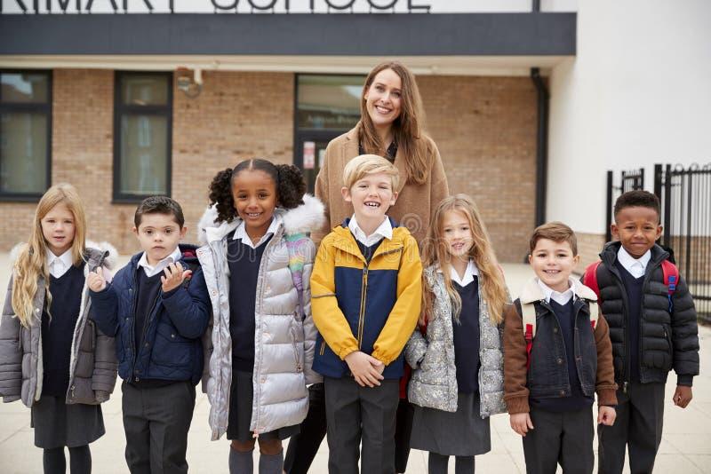 Niños de la escuela primaria que se colocan delante de escuela con su profesor que mira a la cámara, vista delantera imagen de archivo