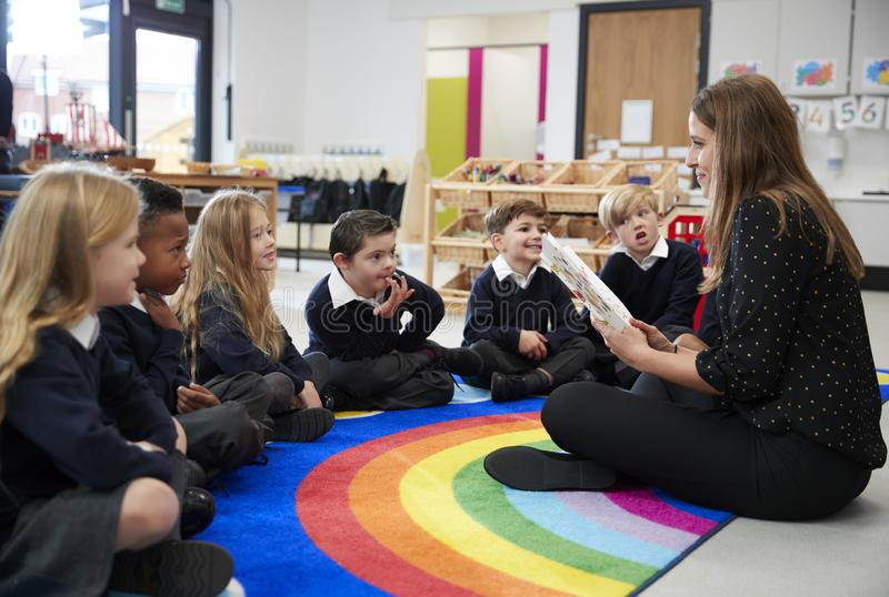 Niños de la escuela primaria que se sientan en el piso en la clase que escucha su maestra que lee un libro a ellos, vista lateral imagenes de archivo
