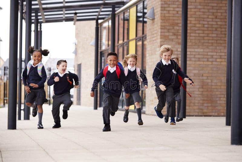 Niños de la escuela primaria, uniformes escolares que llevan y mochilas, corriendo en una calzada fuera de su construcción de esc imagen de archivo
