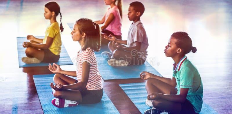 Niños de la escuela que meditan durante clase de la yoga foto de archivo