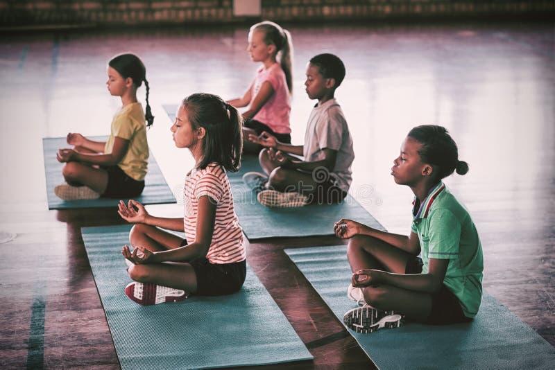 Niños de la escuela que meditan durante clase de la yoga fotos de archivo